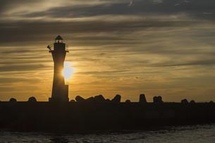 夕焼けのオレンジ色の空にシルエットが映し出される釧路港の灯台の写真素材 [FYI04747645]