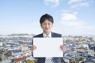 街並みを背景にホワイトボードを掲げたビジネスマンの写真素材 [FYI04748104]
