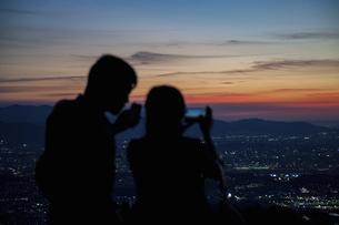 夕景の写真を撮るカップルの後ろ姿の写真素材 [FYI04748160]