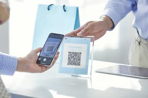 スマートフォンを持ちキャッシュレス決済をする女性の手元と店員の手の写真素材 [FYI04748349]