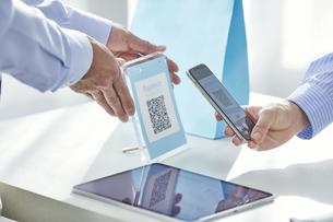 スマートフォンを持ちキャッシュレス決済をする女性の手元と店員の手の写真素材 [FYI04748352]