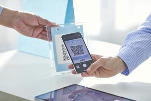 スマートフォンを持ちキャッシュレス決済をする女性の手元と店員の手の写真素材 [FYI04748355]