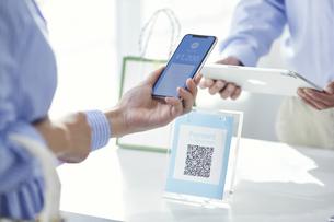 スマートフォンを持ちキャッシュレス決済をする女性の手元と店員の手の写真素材 [FYI04748356]