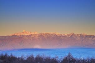 高ボッチ高原から望む朝日に染まる穂高連峰と奥穂高岳に沈む満月の写真素材 [FYI04756611]