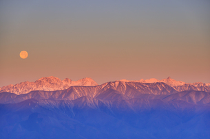 高ボッチ高原から望む朝日に染まる穂高連峰と満月の写真素材 [FYI04756618]