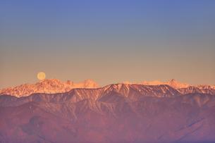 高ボッチ高原から望む朝日に染まる穂高連峰と奥穂高岳に沈む満月の写真素材 [FYI04756622]