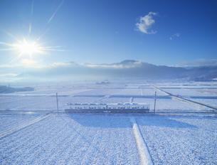 新雪の舞田の田園と別所線のまるまどりーむ号と独鈷山の写真素材 [FYI04756707]