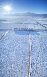 新雪の舞田の田園と別所線の自然と友だち号と独鈷山の写真素材 [FYI04756711]