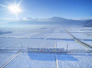 新雪の舞田の田園と別所線の自然と友だち号と独鈷山の写真素材 [FYI04756714]