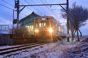夜明けの新雪の八木沢駅に停車する別所線のまるまどりーむ号の写真素材 [FYI04756719]
