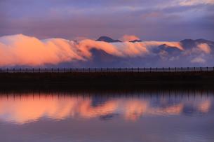 朝日に染まる太郎山の逆さ霧と水鏡の舌喰池の写真素材 [FYI04756754]