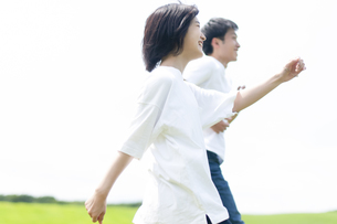 草原を歩くカップルの写真素材 [FYI04760345]