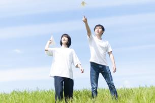 草原で紙ヒコーキを飛ばすカップルの写真素材 [FYI04760351]