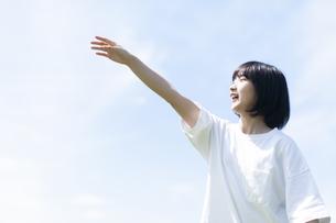 草原で紙ヒコーキを飛ばす女性の写真素材 [FYI04760357]