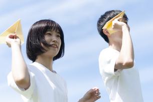 紙ヒコーキを飛ばすカップルの写真素材 [FYI04760363]