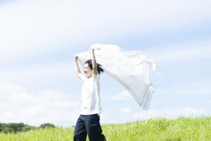 草原で布を風になびかせる女性の写真素材 [FYI04760382]