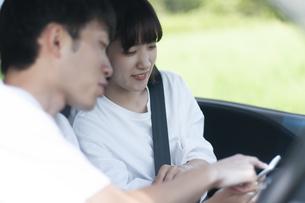 車内でスマホを見るカップルの写真素材 [FYI04760417]