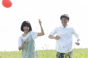 草原で遊ぶカップルの写真素材 [FYI04760457]
