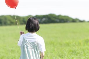 草原で赤い風船を持つ女性の後ろ姿の写真素材 [FYI04760458]