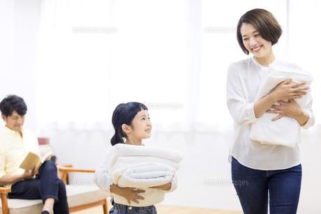 洗濯物をたたむ親子の写真素材 [FYI04760707]