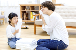 洗濯物をたたむ親子の写真素材 [FYI04760710]