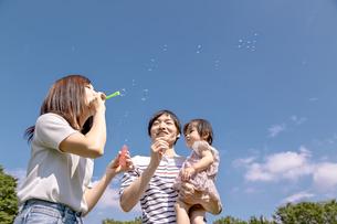 青空を背景にシャボン玉で遊ぶ幸せな親子の写真素材 [FYI04761353]