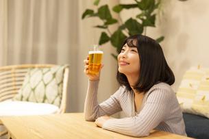 夜の部屋でビールを飲む若い女性の写真素材 [FYI04762142]