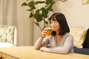 夜の部屋でビールを飲む若い女性の写真素材 [FYI04762143]