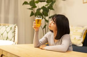 夜の部屋でビールを飲む若い女性の写真素材 [FYI04762145]