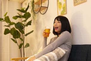 夜の部屋でビールを飲む若い女性の写真素材 [FYI04762148]