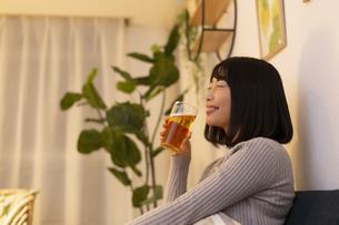 夜の部屋でビールを飲む若い女性の写真素材 [FYI04762150]