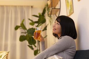 夜の部屋でビールを飲む若い女性の写真素材 [FYI04762151]