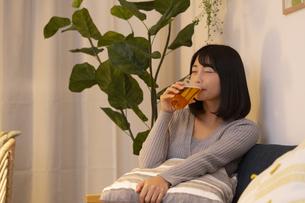 夜の部屋でビールを飲む若い女性の写真素材 [FYI04762152]