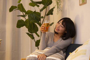 夜の部屋でビールを飲む若い女性の写真素材 [FYI04762153]