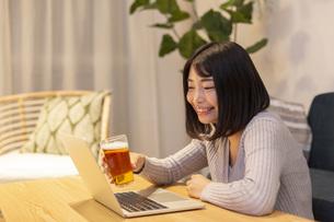 夜の部屋でパソコンを見ながらビールを飲む若い女性の写真素材 [FYI04762156]