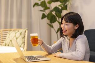 夜の部屋でパソコンを見ながらビールを飲む若い女性の写真素材 [FYI04762159]