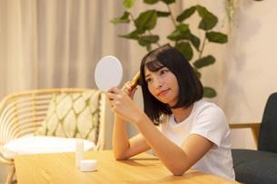 夜の部屋で美容ケアをする若い女性の写真素材 [FYI04762171]