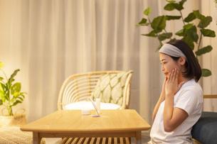 夜の部屋で美容ケアをする若い女性の写真素材 [FYI04762181]