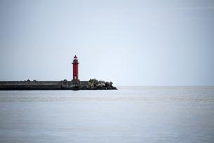 青く静かな空と海の間の防波堤に建っている赤い灯台の写真素材 [FYI04762232]