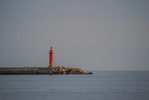 穏やかな夕暮れの港に立つ赤い灯台の写真素材 [FYI04762235]