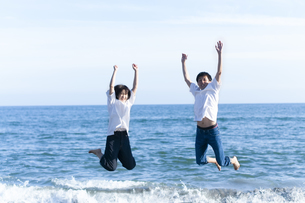 海でジャンプするカップルの写真素材 [FYI04763675]