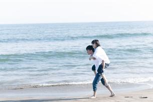 海辺で恋人を背負う男性の写真素材 [FYI04763680]