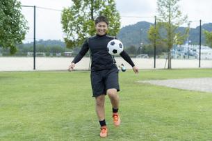 公園でサッカーをする若い男性の写真素材 [FYI04764238]