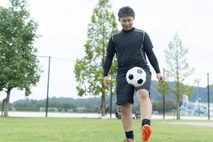 公園でサッカーをする若い男性の写真素材 [FYI04764239]