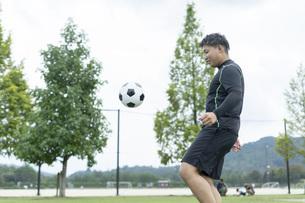 公園でサッカーをする若い男性の写真素材 [FYI04764240]