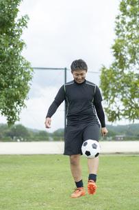 公園でサッカーをする若い男性の写真素材 [FYI04764241]