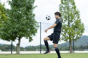 公園でサッカーをする若い男性の写真素材 [FYI04764242]
