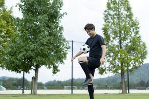 公園でサッカーをする若い男性の写真素材 [FYI04764243]