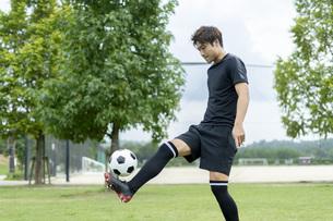 公園でサッカーをする若い男性の写真素材 [FYI04764244]