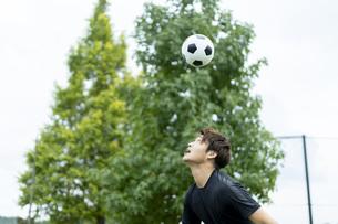公園でサッカーをする若い男性の写真素材 [FYI04764246]
